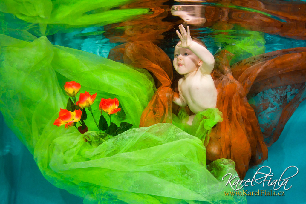 Dítě loví květiny pod vodou při plavání vbaby klubu